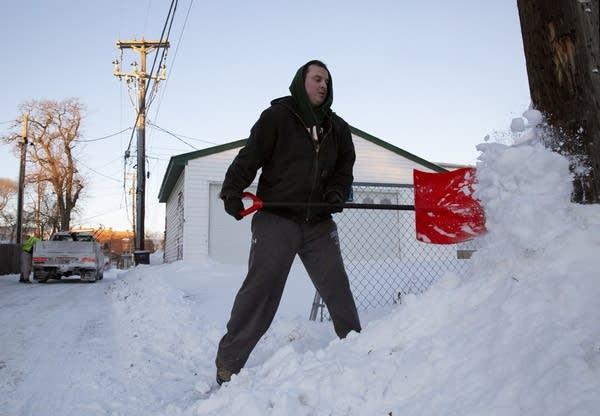 A man shoveling snow from a sidewalk.
