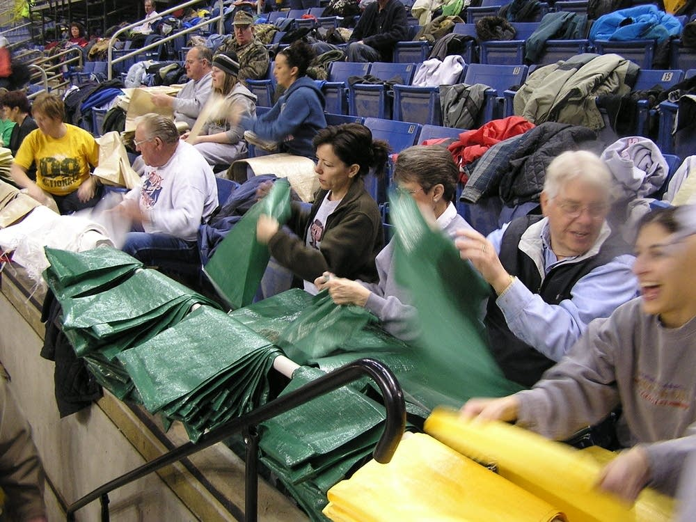 Volunteers fold and prep sandbags to be filled
