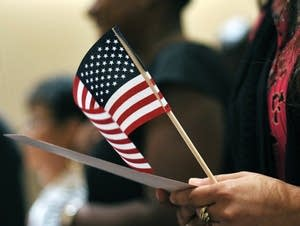 Newly sworn-in U.S. citizens recite the Pledge of Allegiance