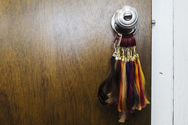 Colored hair swatches hang from a door knob.