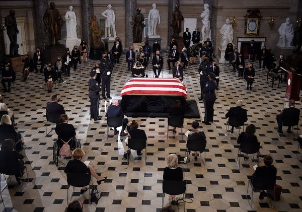 People stand around a flag-draped casket.