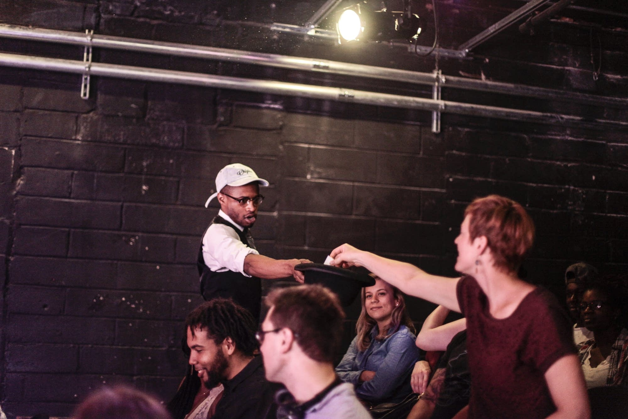 Kory Laquess Pullam gives the swag hat to an audience member.