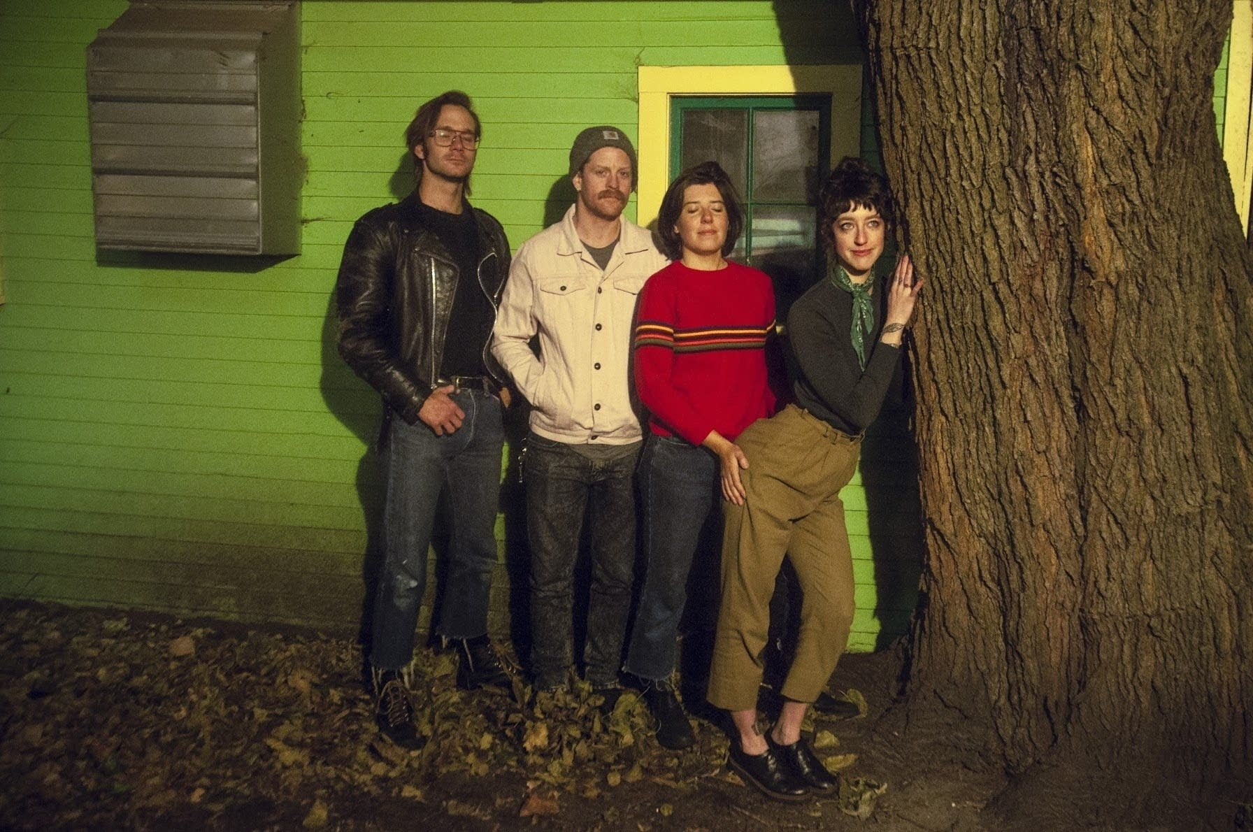 Four people standing near a tree at night.
