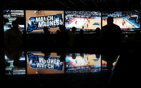 People watch coverage of the NCAA college basketball tournament.
