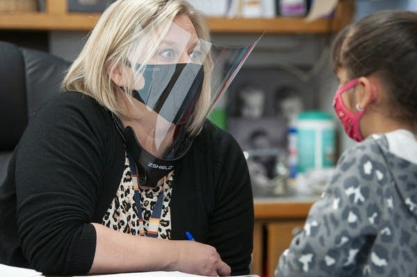 A teacher wears a face shield and face mask.