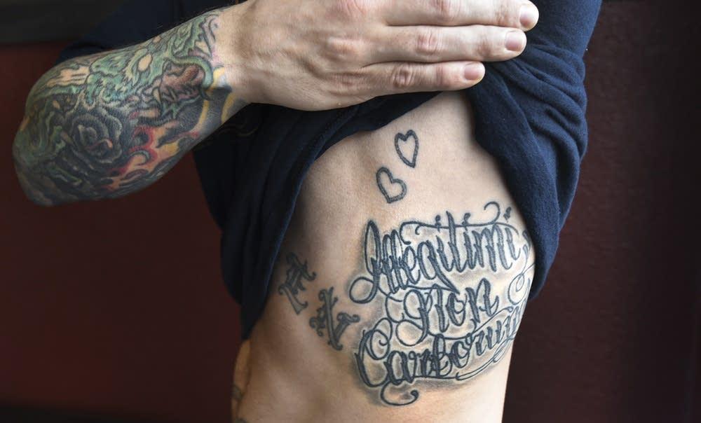 Displaying a tattoo on his torso