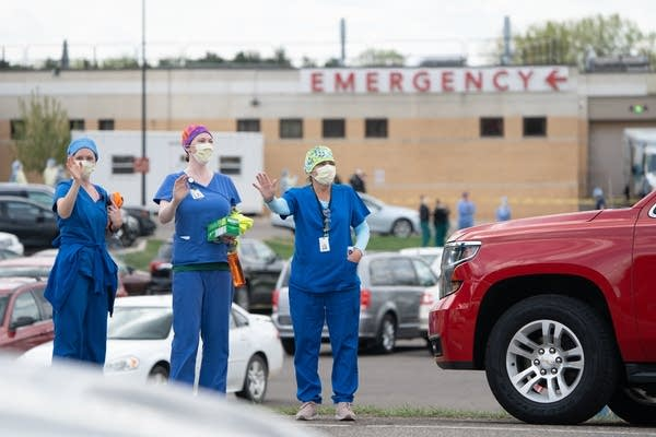 People in scrubs wave at cars.