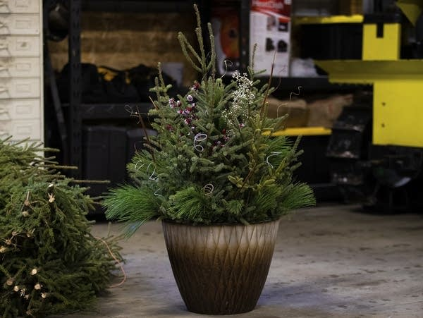 An arrangement of greenery and sparkling decorations in a pot.