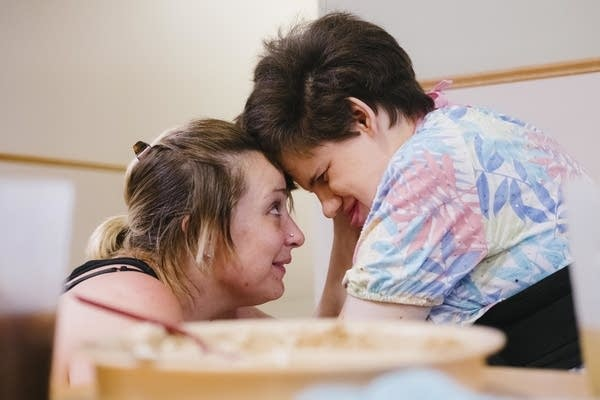 Caregiver Cat McNamara looks into Sarah Gonella's eyes.