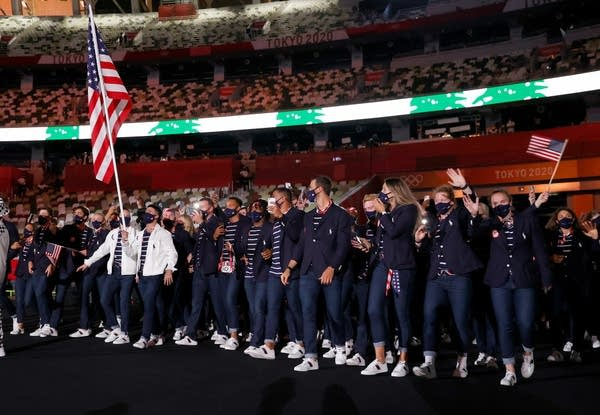 Two flag bearers lead their team during the Olympic opening ceremony.