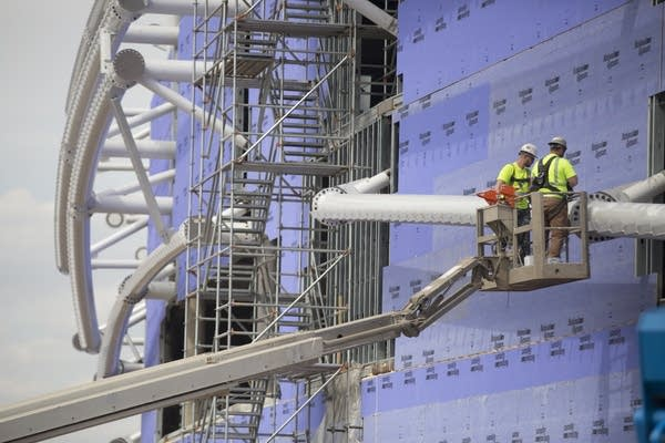 Construction workers fasten steel beams to the outside of the stadium.