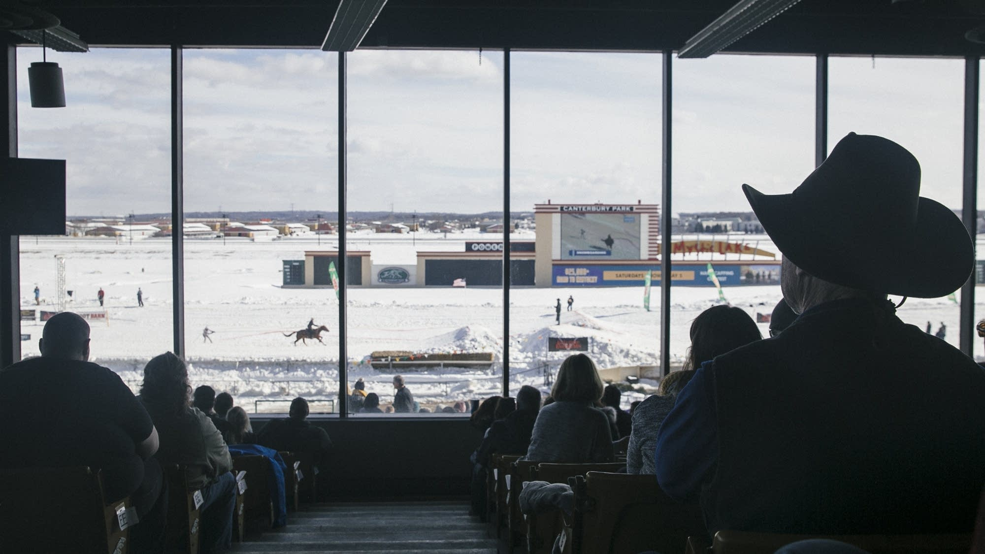 Spectators keep warm inside of Canterbury Park's stands.