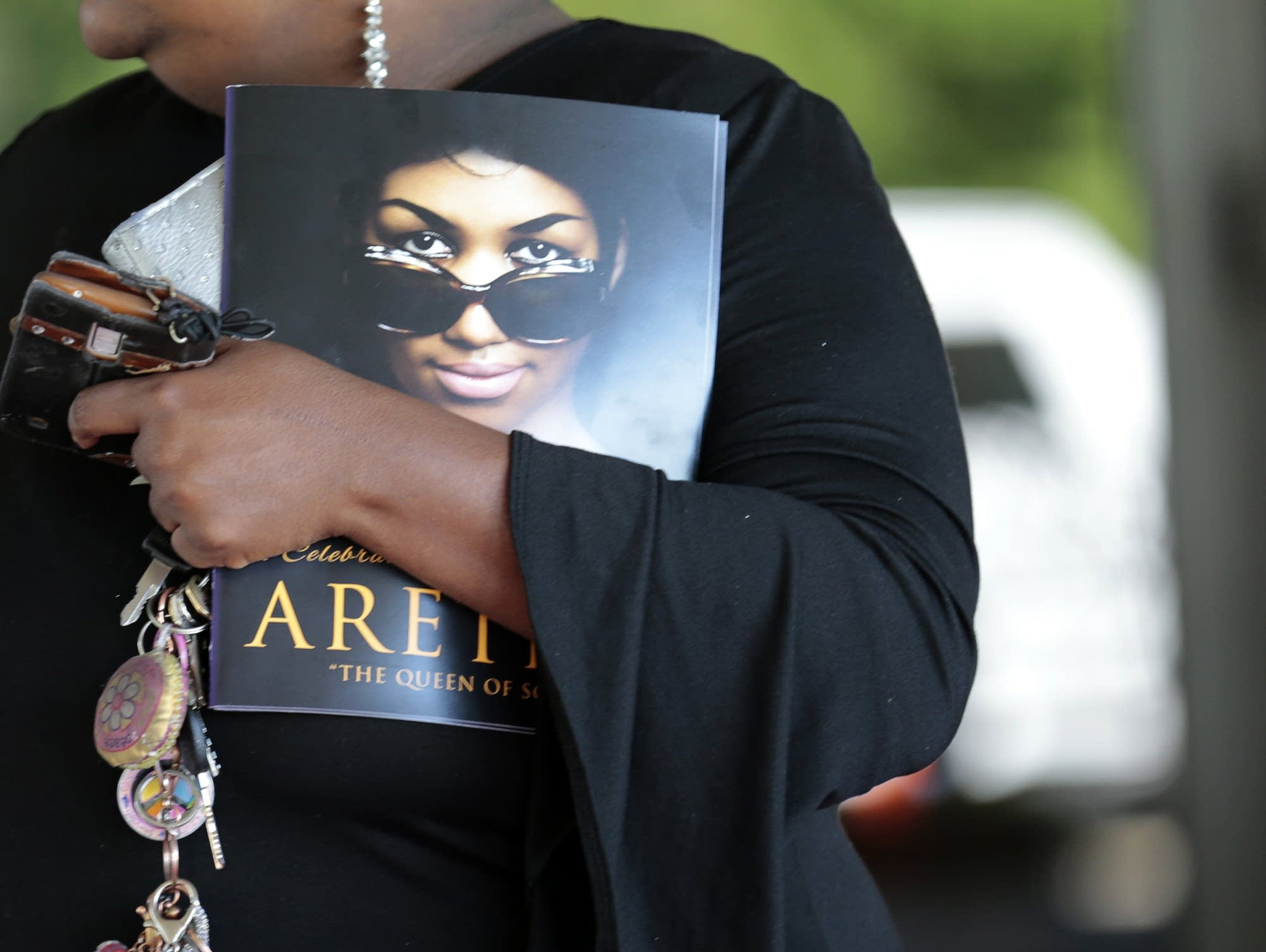 A woman holds a program from Aretha Franklin's funeral.
