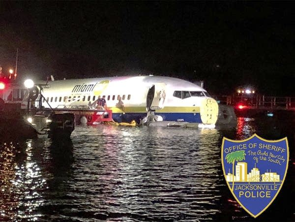 Authorities work at the scene where a plane slid into a river