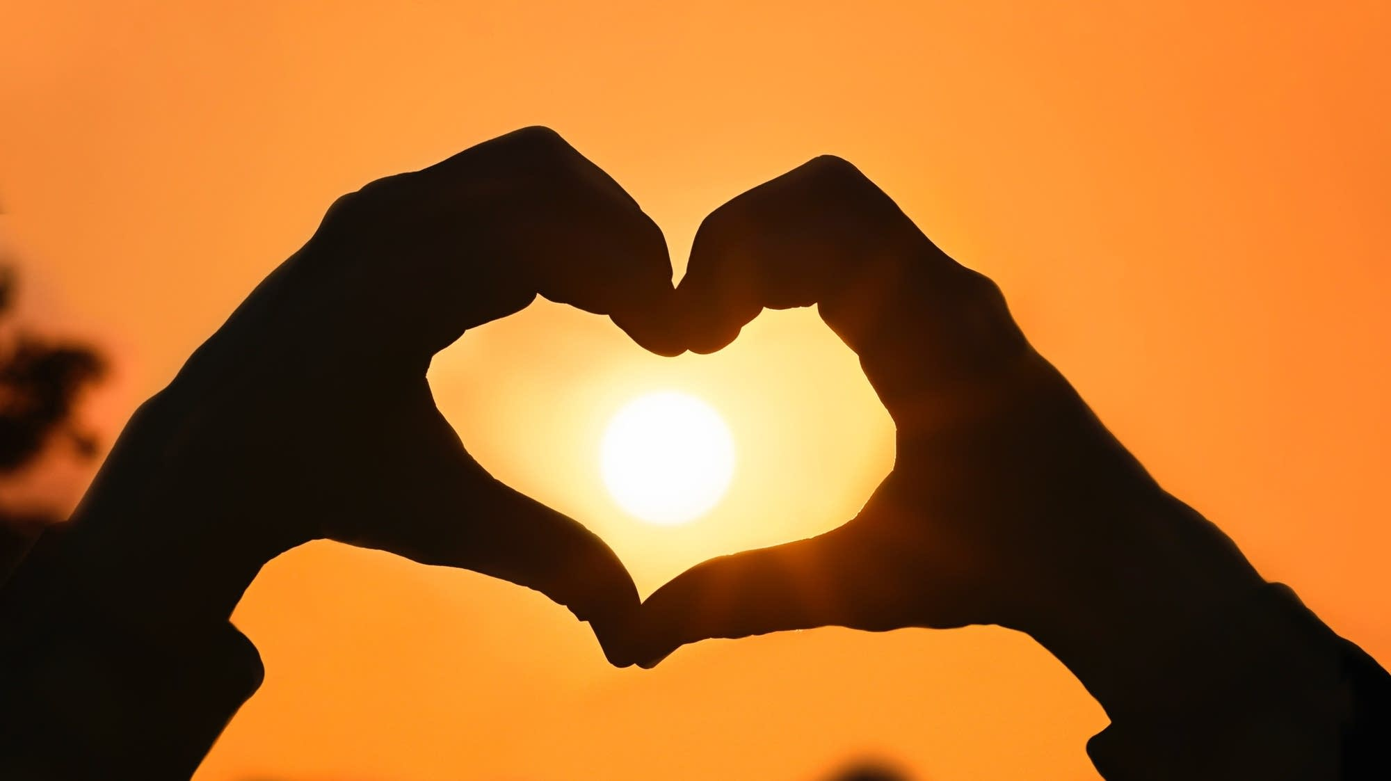 Heart-shaped hands at sunset.