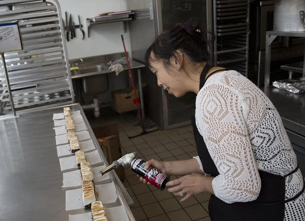 A woman uses a small blowtorch to caramelize desserts.