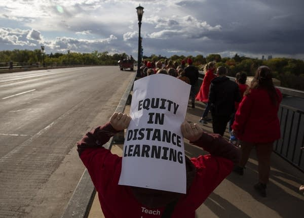 "A person holding a sign that reads ""equity in distance learning."""