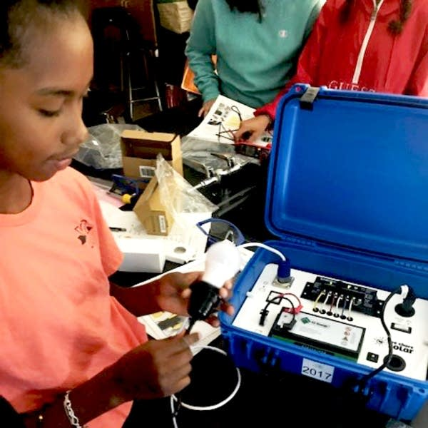 A student works on assembling a solar suitcase.