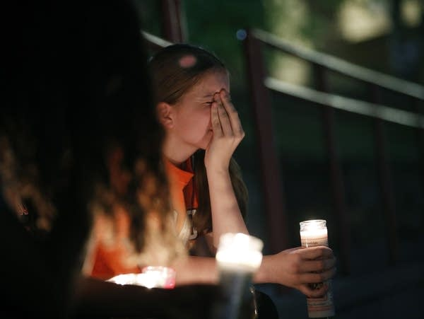 Sherie Gramlich reacts during a vigil for victims of a mass shooting