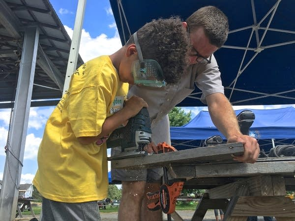 Kids work with power tools to make sculptures under supervision.