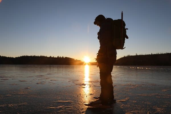 Sven Hoaglund inspects the ice at sunrise in the Boundary Water.