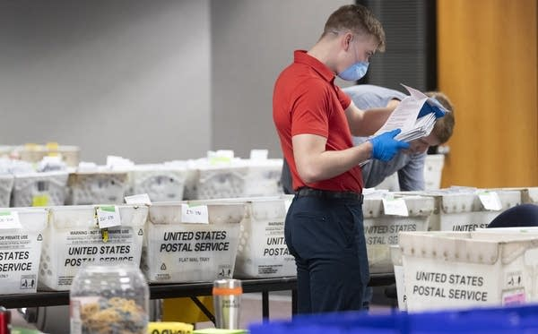 Milwaukee election commission worker processes and sorts absentee ballots