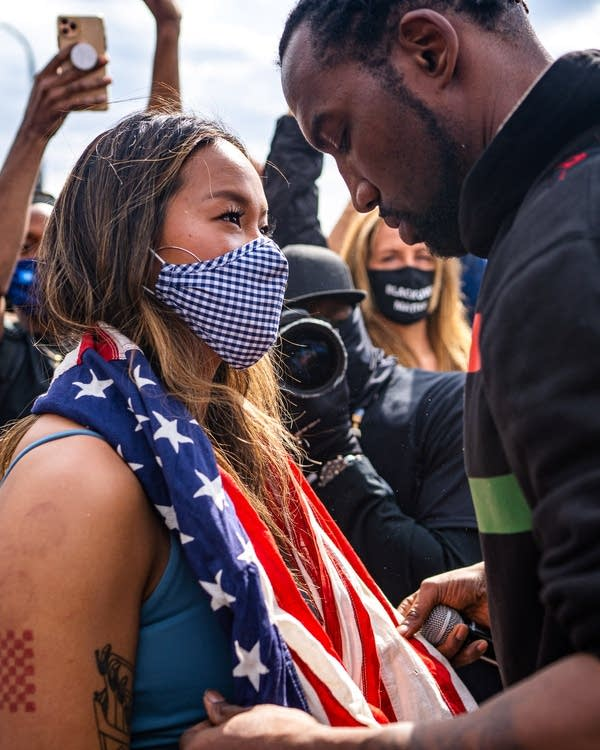 A man drapes a US flag around the neck of a woman.