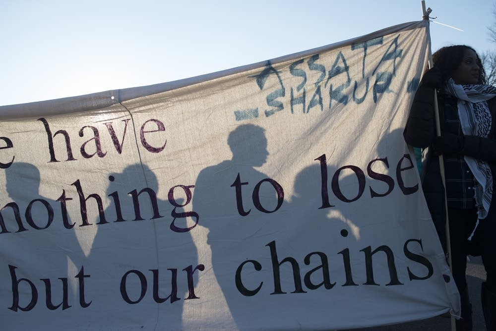 Protesters are silhouetted against a banner.