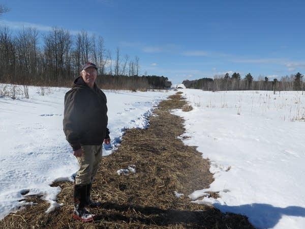 Richard Shustarich stands above an oil pipeline