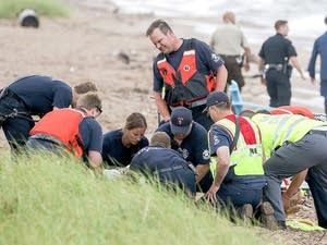 Emergency personnell administer CPR to a girl pulled from Lake Superior