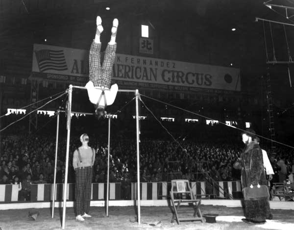 Dudley Riggs, spotting his father on the bars,