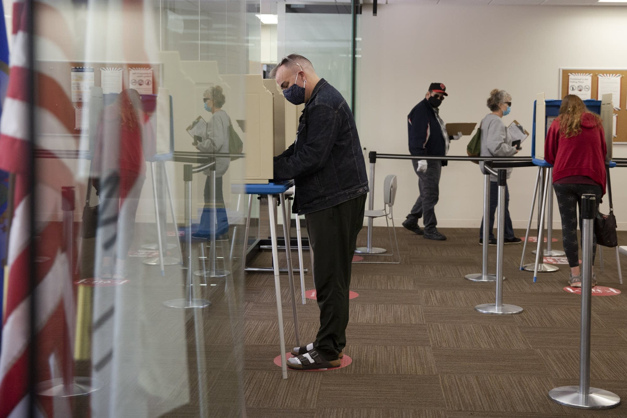 People standing at voting booths that are distanced apart from each other.