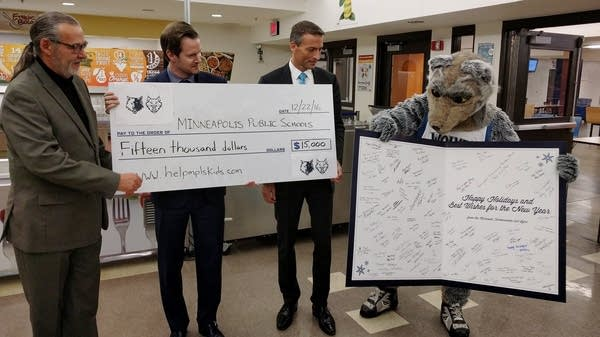 Wolves and Lynx CEO Ethan Casson presents a donation.