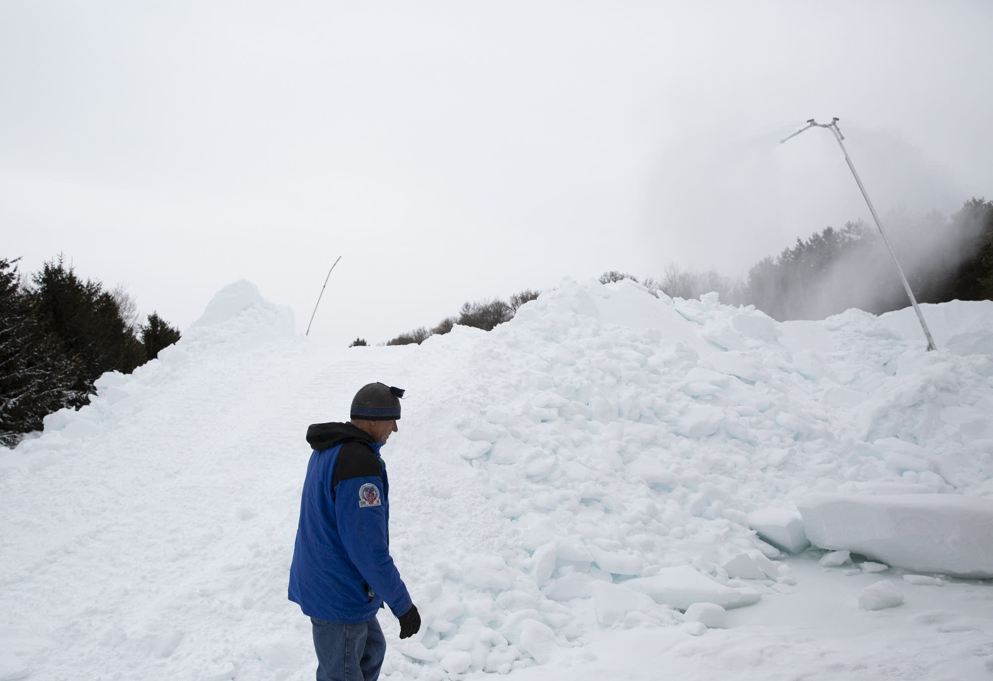 Volunteer Don Olson walks past a mound of artificial snow.