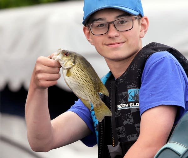 Carter Jensen of Rothsay, Minn., holds up a freshly caught rock bass.