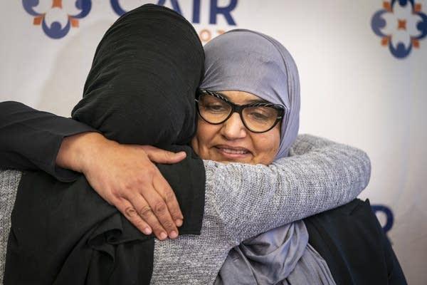 A woman hijab hugs another woman.