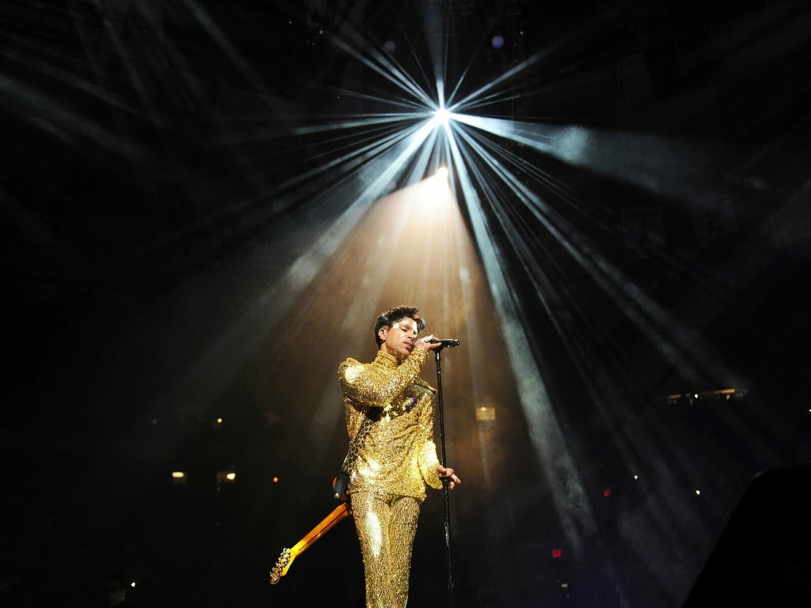 Prince performing onstage under a spotlight