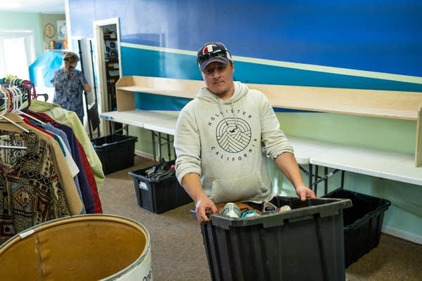 Johnny Petty carries a box of donated shoes into the basement