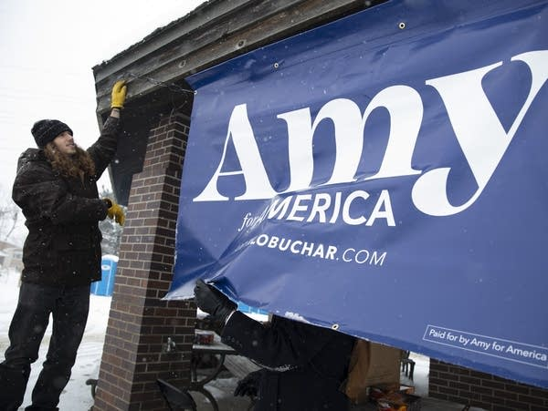 "Bjorn Sorenson of St. Paul, Minn., hangs up an ""Amy for America"" sign"