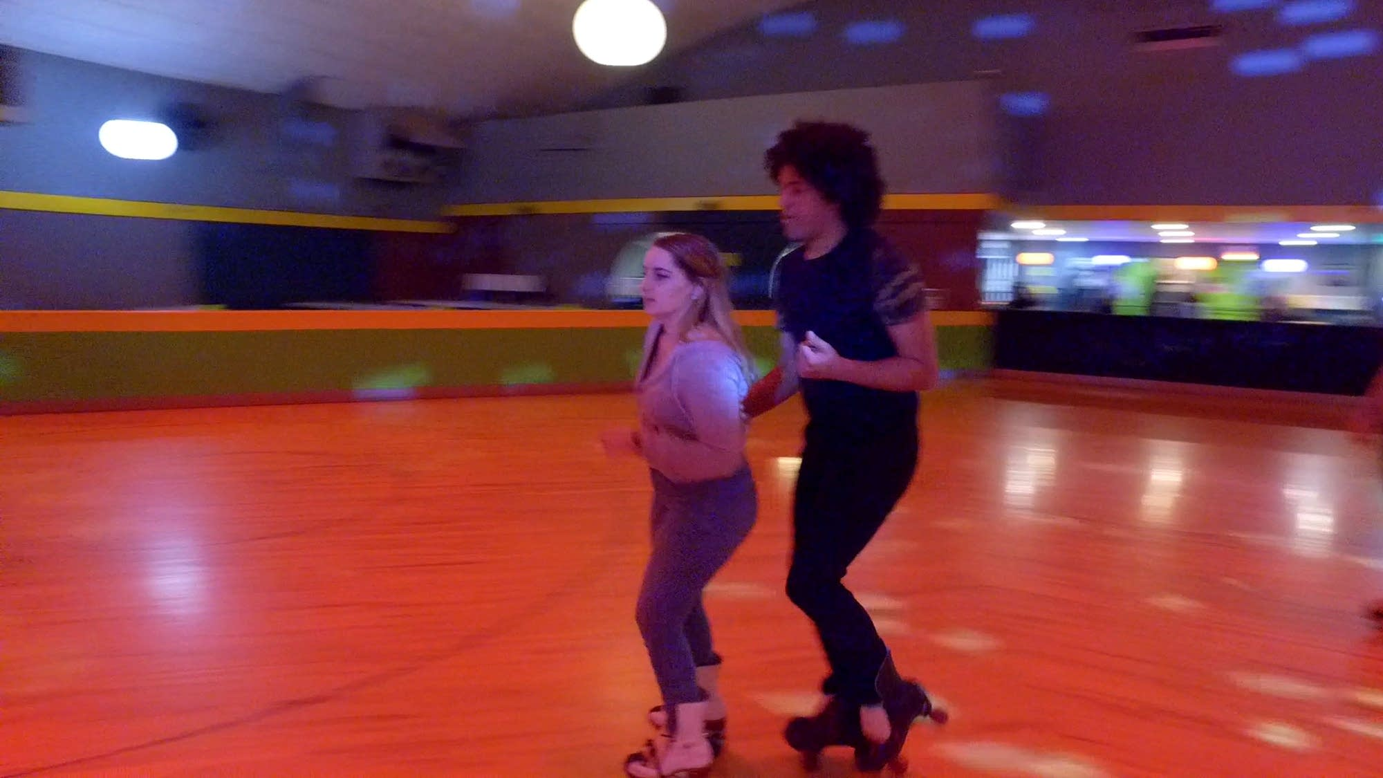 Two people roller skate side by side.