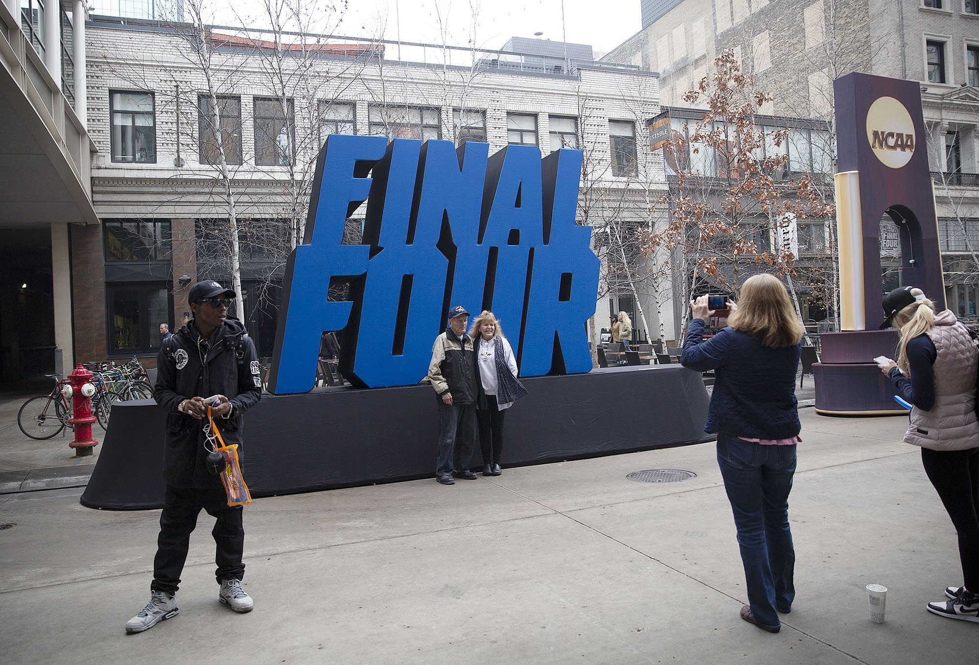 Fans take photos in front of a Final Four sign at Nicollet Mall.
