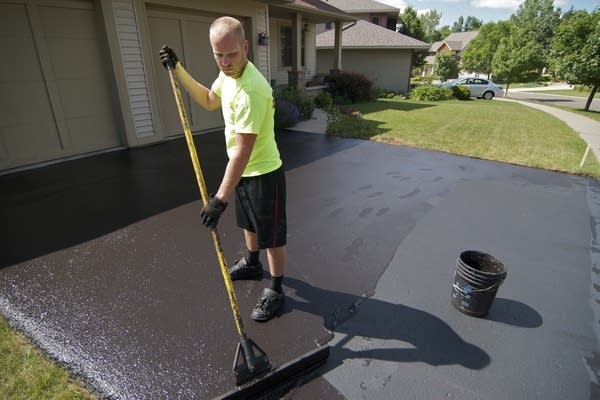 A coal tar-based sealant is applied on a driveway.