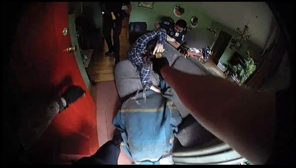 Officers try to subdue a man falling over a upturned couch.
