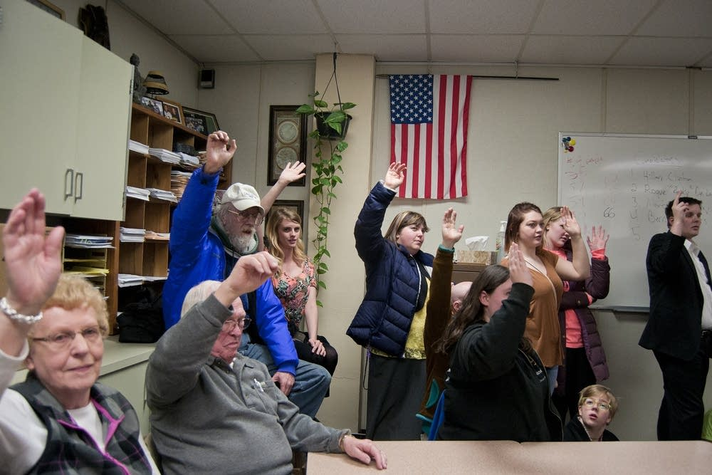Caucus-goers raise their hands to be counted.