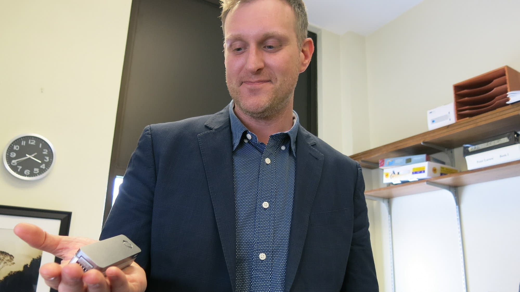 Research professor Peter Larsen holds a DNA sequencer