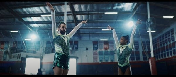 Jonathan Van Ness and Simone Biles in leotards doing gymnastics in a gym