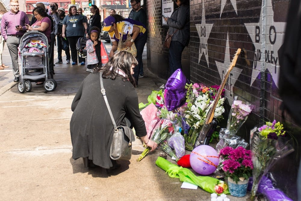 A mourner places a bouquet of flowers at First Ave