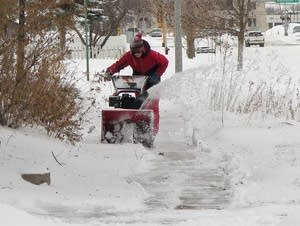 A person uses a snowblower on the sidewalk in Brainerd.