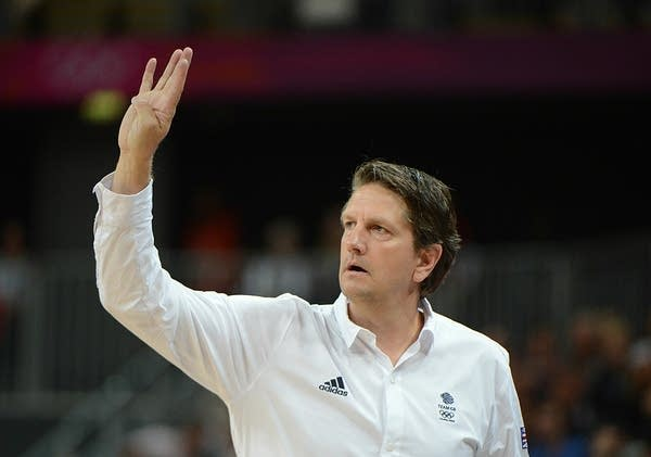 A man gestures on a basketball court.