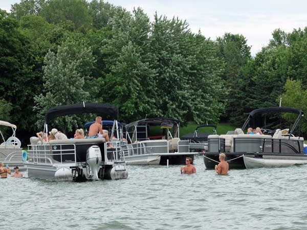 people swim while others sit on a pontoon boat